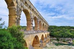 Pont du Gard. Remoulins, France - Jul 19, 2014: Tourists have a rest on the shore of Gardon river under an old Roman aqueduct Pont du Gard. The Gorge du Gardon Royalty Free Stock Photos