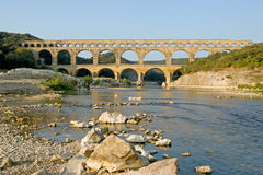 Pont du Gard with Rocky Shoreline. This shot of the Roman aqueduct bridge was taken at sunrise in Provence, France Stock Photos