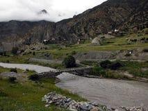 Pont en bois au-dessus d'une rivière de l'Himalaya Photos stock