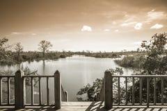 Pont en bois avec la vue panoramique sur la rivière menant à l'horizon, avec les banques en crue images libres de droits