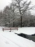 Pont en bois isolé d'hiver au-dessus de rivière de forêt Images stock