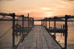 Pont en bois sur la plage et le beau coucher du soleil près de la mer Photographie stock libre de droits