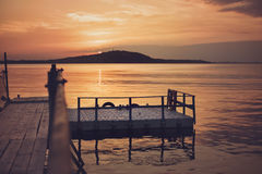 Pont en bois sur la plage et le beau coucher du soleil près de la mer Filtre supplémentaire Photo stock
