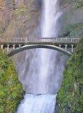 Pont en ciment croisant au-dessus de la cascade puissante Image libre de droits