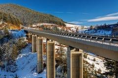 Pont en montagne en hiver avec la neige et le ciel bleu Photographie stock