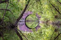 Pont en pierre dans les arbres denses avec la r?flexion en rivi?re photographie stock