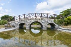 Pont en pierre très vieux au-dessus du lac tranquille avec sa réflexion dans l'eau photo libre de droits