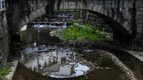 Pont en pierre très vieux au-dessus du lac tranquille avec sa réflexion dans l'eau Image libre de droits