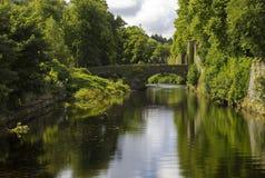 Pont en rue de château et le mur de château par la rivière de bras Photos stock