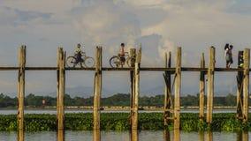 Pont en teck et deux hommes avec des vélos Images libres de droits