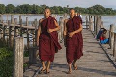 Pont en teck et moines de marche photo stock