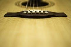 Pont et ficelles en selle de guitare acoustique Photo stock