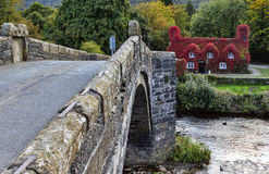 Pont Fawr. Famous medieval stone bridge across the river Conwy, and court house covered in red ivy Stock Images