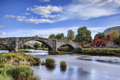 Pont Fawr. Famous medieval stone bridge across the river Conwy, and court house covered in red ivy Royalty Free Stock Images
