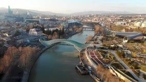 pont mou d'horizon de lumière de matin d'infrastructure moderne de la vue 4k aérienne au-dessus de la rivière Tbilisi, la G?orgie banque de vidéos
