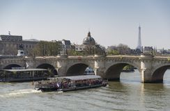 Pont Neuf and Seine river with tour boat in Paris, France. PARIS - FRANCE, 2015: Consiergerie, Pont Neuf and Seine river with tour boat at sunny summer sunset on stock images