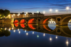 Pont Neuf in Toulouse. Evening view of historic Pont Neuf in Toulouse, France, with illuminated arches over Garonne River Stock Image