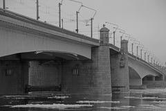 Pont noir et blanc au-dessus de la rivière avec les banquises de flottement images libres de droits