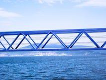 Pont peint de bleu de fer au-dessus de l'eau de mer Photos libres de droits
