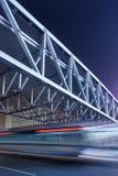 Pont piétonnier avec l'autobus dans la tache floue de mouvement la nuit, Pékin, Chine Photos libres de droits