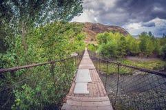 Pont piétonnier de vieille suspension au-dessus de rivière lentille de fisheye de perspective de déformation photos stock