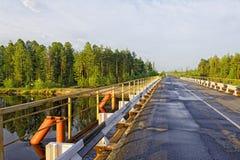 Pont renforcé en route bétonnée à travers la rivière sibérienne de taiga Images stock