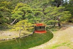 Pont rouge au-dessus de courant de jardin Image stock
