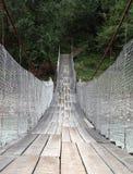 Pont suspendu à travers la rivière de montagne Images libres de droits
