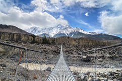 Pont suspendu à travers la rivière de montagne en Himalaya Photo stock