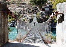 Pont suspendu accrochant de corde au Népal Photographie stock libre de droits