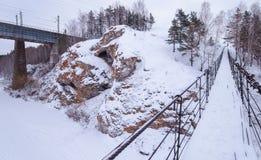 Pont suspendu au-dessus d'une rivière congelée avec les banques rocheuses image libre de droits
