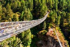 Pont suspendu au-dessus de la rivière en montagnes de l'Himalaya, Népal photographie stock