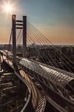 Pont suspendu au point de repère moderne urbain de coucher du soleil Photo libre de droits