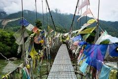 Pont suspendu de marche avec beaucoup de drapeaux colorés de prière dedans images stock