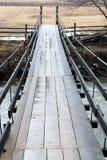 Pont suspendu en bois au-dessus de rivière de forêt de montagnes image libre de droits
