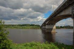 Pont vers la banque opposée de la rivière, sous le ciel nuageux au printemps Image libre de droits