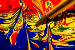 Ponta da escova do artista que mergulha em uma mistura de cores preliminares que formam um teste padrão de roda vibrante do caos foto de stock