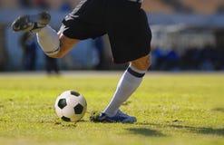 Pontapé do goleiros do jogador de futebol a bola durante o fósforo de futebol Fotografia de Stock Royalty Free