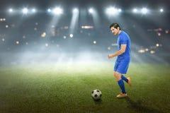 Pontapé masculino asiático vigoroso do jogador de futebol a bola Foto de Stock