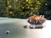 Pontas de cigarro em um cinzeiro de vidro. imagens de stock royalty free