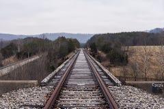 Ponte abandonada da estrada de ferro - opinião da trilha na tarde nebulosa imagem de stock royalty free