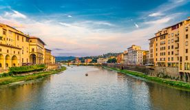 Ponte alle Grazie stone bridge and boat on Arno River water and embankment promenade with buildings in Florence historical centre stock photos