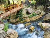 Ponte arancio per attraversare un bello e piccolo fiume variopinto in Vang Vieng, Laos fotografia stock