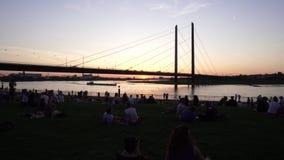 Ponte através do por do sol de Rhine River, Dusseldorf, Alemanha filme