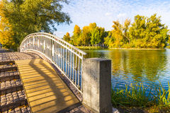Ponte attraverso lo stagno con le isole nel parco di autunno Immagini Stock