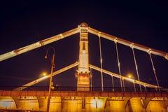 A ponte bonita longa através do rio na noite foto de stock royalty free