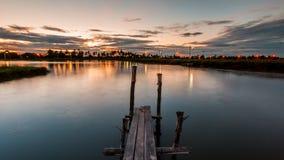 Ponte boscoso nel porto al tramonto Fotografia Stock