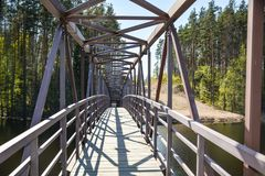 Ponte a céu aberto do metal à igreja no rio Vuoksa foto de stock
