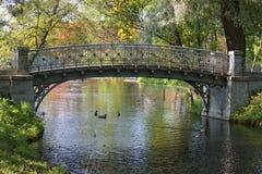 Ponte a céu aberto do metal sobre o canal Parque de Gatchina, região de Leninegrado imagem de stock royalty free