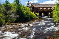 Ponte coberta sobre o córrego do rio fotos de stock